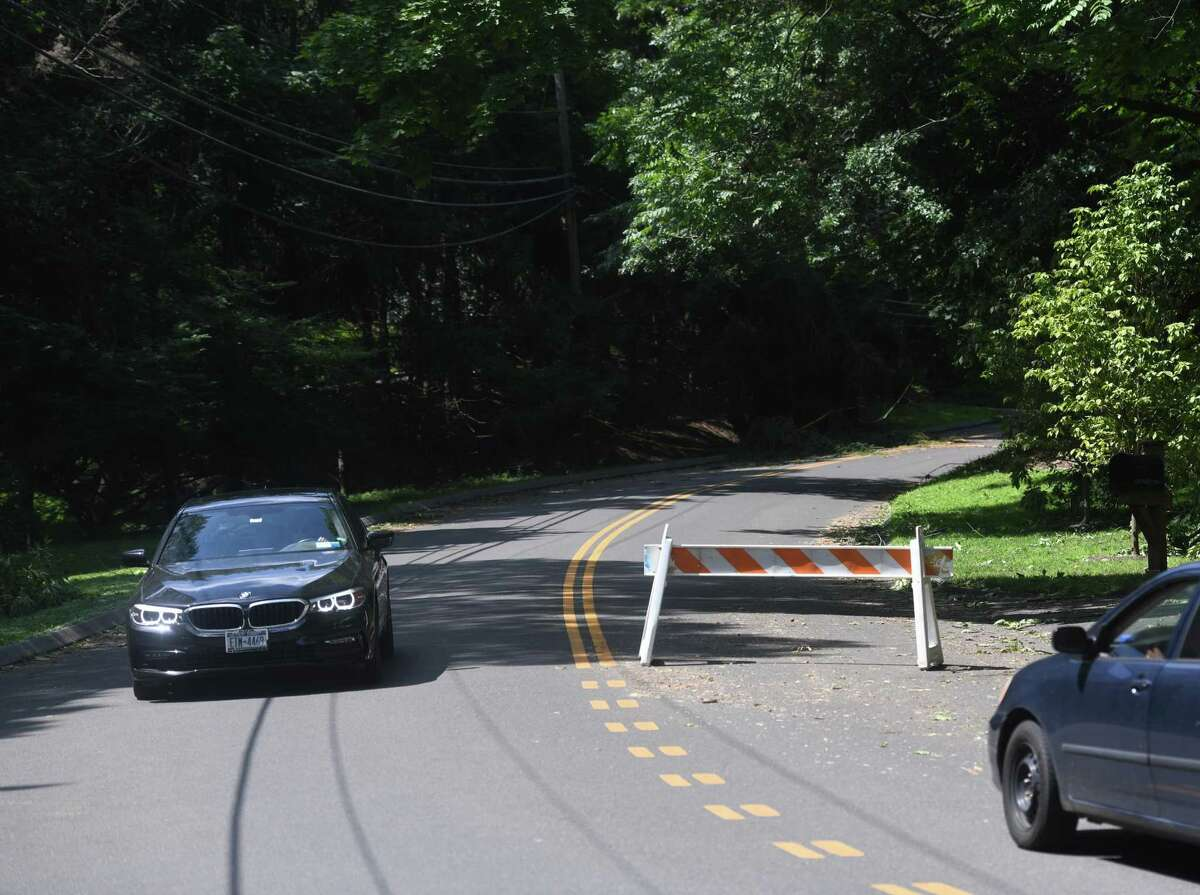 Edgewood Drive is closed as downed trees from tropical storm Isaias remain on the road in Greenwich, Conn. Wednesday, Aug. 5, 2020. Tuesday's storm knocked down trees and powerlines throughout the state and power remains out in thousands of homes.