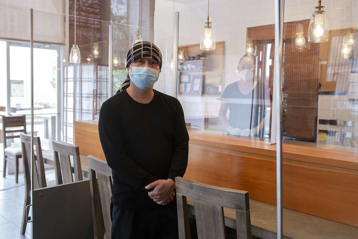 Chikara Ono, owner of Delage restaurant, stands for a portrait at Delage in Oakland, Calif. on Wednesday, August 5, 2020 along with his head chef Mikiko Ando. Delage is one of a few omakase restaurants that are installing plexiglass shields around their sushi bars in hopes of being able to reopen in the coming months.