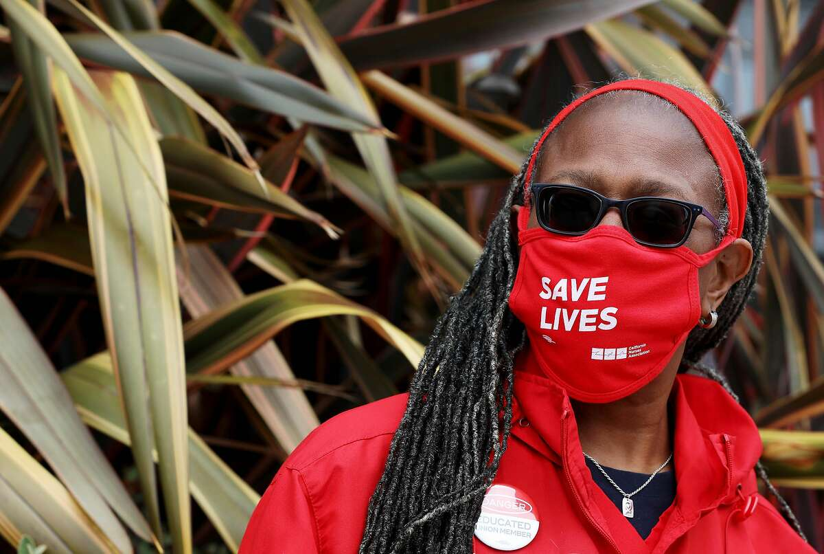 """Tora R. Spigner, a registered nurse, dons a """"Save Lives"""" mask during a protest outside the Alta Bates Summit Medical Center on Wednesday, August 5, 2020, in Oakland, Calif. As firsthand witnesses and actual victims during this COVID-19 crisis of a health care and economic system that prioritizes money over people, members of California Nurses Association (CNA) and the Caregiver and Health Care Employees Union (CHEU) who work as registered nurses, respiratory therapists, lab and other technicians, and in other health care capacities held the event that included more than 200 protests across the United States to demand that their elected leaders, government, and hospital employers take immediate action to save lives."""