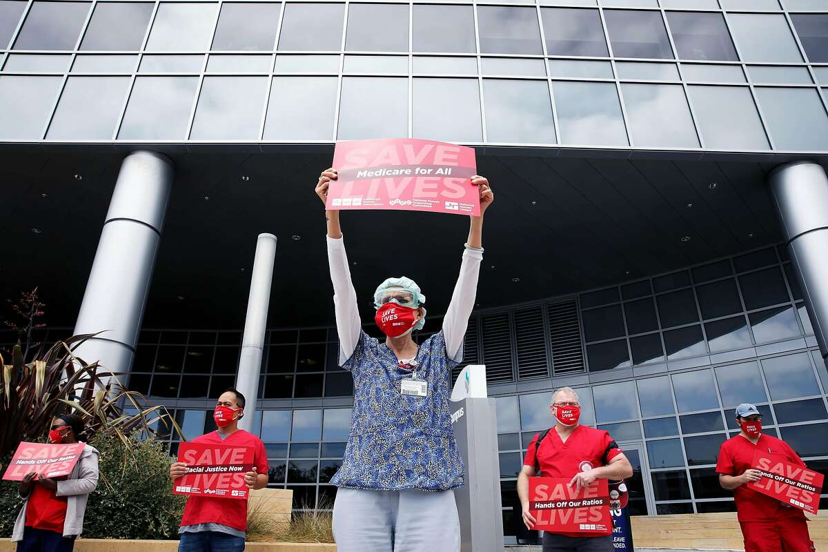 """Leslie Blanchard, a registered nurse, lifts a """"Save Lives. Medicare for All,"""" sign during a protest outside the Alta Bates Summit Medical Center on Wednesday, August 5, 2020, in Oakland, Calif. As firsthand witnesses and actual victims during this COVID-19 crisis of a health care and economic system that prioritizes money over people, members of California Nurses Association (CNA) and the Caregiver and Health Care Employees Union (CHEU) who work as registered nurses, respiratory therapists, lab and other technicians, and in other health care capacities held the event that included more than 200 protests across the United States to demand that their elected leaders, government, and hospital employers take immediate action to save lives."""