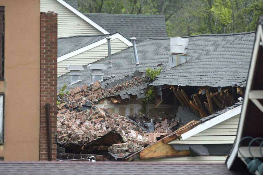 A building partially collapsed onto another in downtown Bethel due to furious wind from Tropical Storm Isaias on Tuesday. The material from the collapsed building damaged the roof to the Village Square building. Photo: H John Voorhees III / Hearst Connecticut Media
