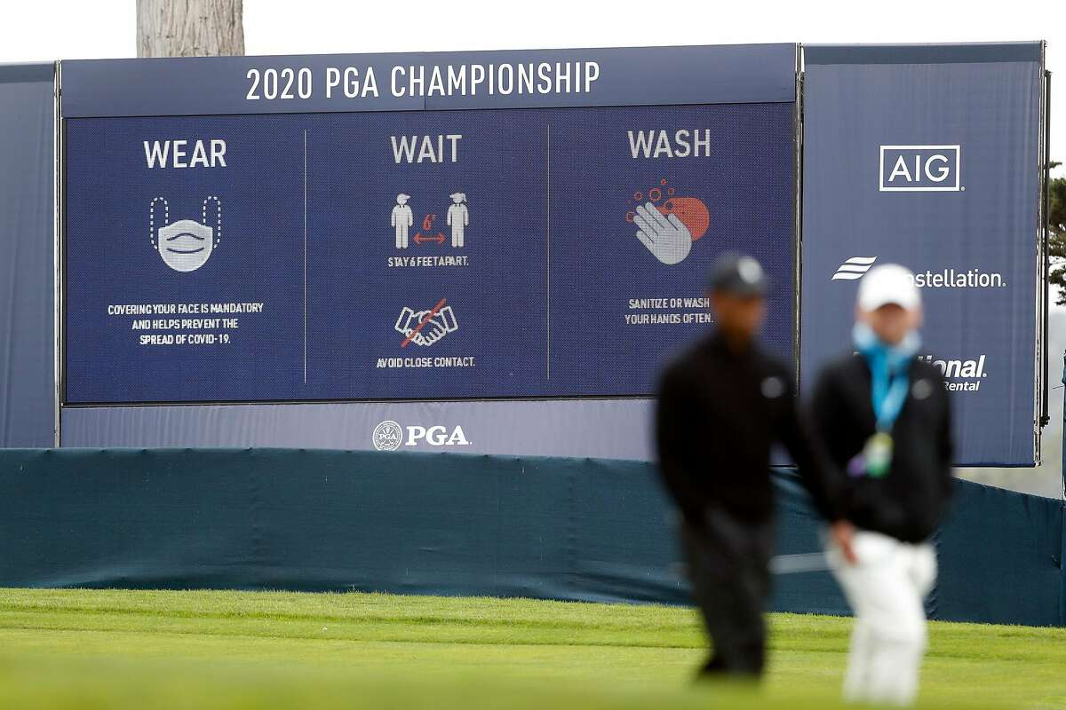 A COVID-19 message on video board as Tiger Woods walks past during PGA Championship practice round at Harding Park in San Francisco, Calif., on Wednesday, August 5, 2020.