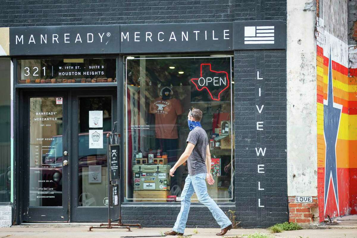 """Pedestrians walk past Manready Mercantile next to a vacant lot along 19th Street in the Heights, Wednesday, Aug. 5, 2020, in Houston. A developer hoping to build in the empty lot had to approach the planning commission for a reprieve when they found that existing regulations would have forced them to build 25 feet back from the street. The city passed a """"walkable places"""" ordinance Wednesday to allow more pedestrian-friendly buildings in certain pockets of Houston."""
