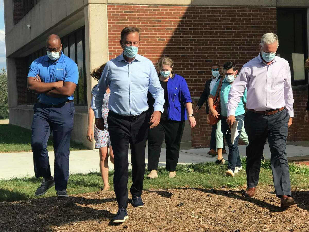 Gov. Ned Lamont responded sternly to the 800,000 power outages in the Connecticut territory of Energy after Isaias. He's shown at the Eversource operations center in Berlin with his staff, walking out of a meeting at the company, with Craig Hallstrom, far right, president of Eversource's electric operations; and Lamont is shown speaking with Hallstrom at left.