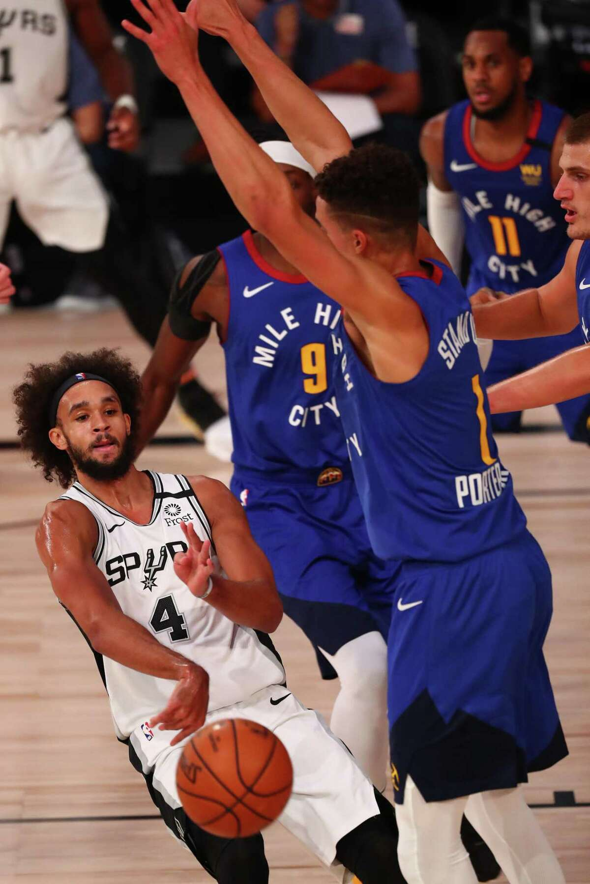 The Spurs' Derrick White (4) passes around the Nuggets' Michael Porter Jr. during the second half Wednesday at the Visa Athletic Center in Lake Buena Vista, Fla. White finished with 23 points and seven assists in the loss.