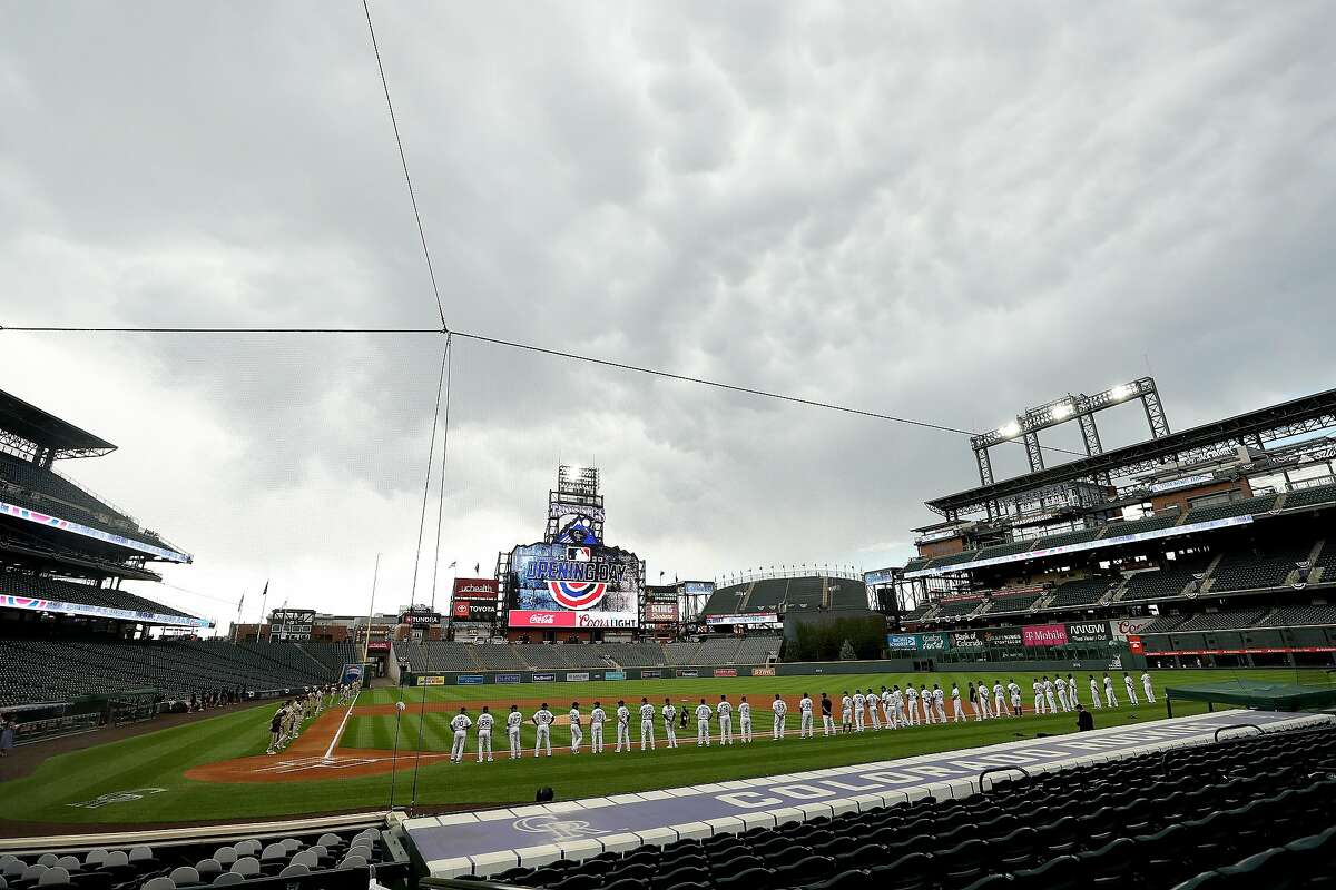 DENVER, COLORADO - JULY 31: Members of the San Diego Padres and the Colorado Rockies stand for the National Anthem before their game at Coors Field on July 31, 2020 in Denver, Colorado. (Photo by Matthew Stockman/Getty Images)