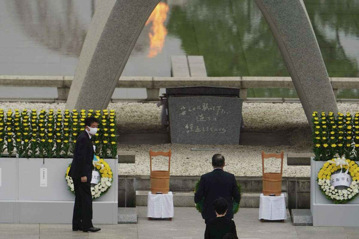 Japanese Prime Minister Shinzo Abe offers flowers to Hiroshima Memorial Cenotaph during a ceremony to mark the 75th anniversary of the bombing at the Hiroshima Peace Memorial Park Thursday, Aug. 6, 2020, in Hiroshima, western Japan. (AP Photo/Eugene Hoshiko)