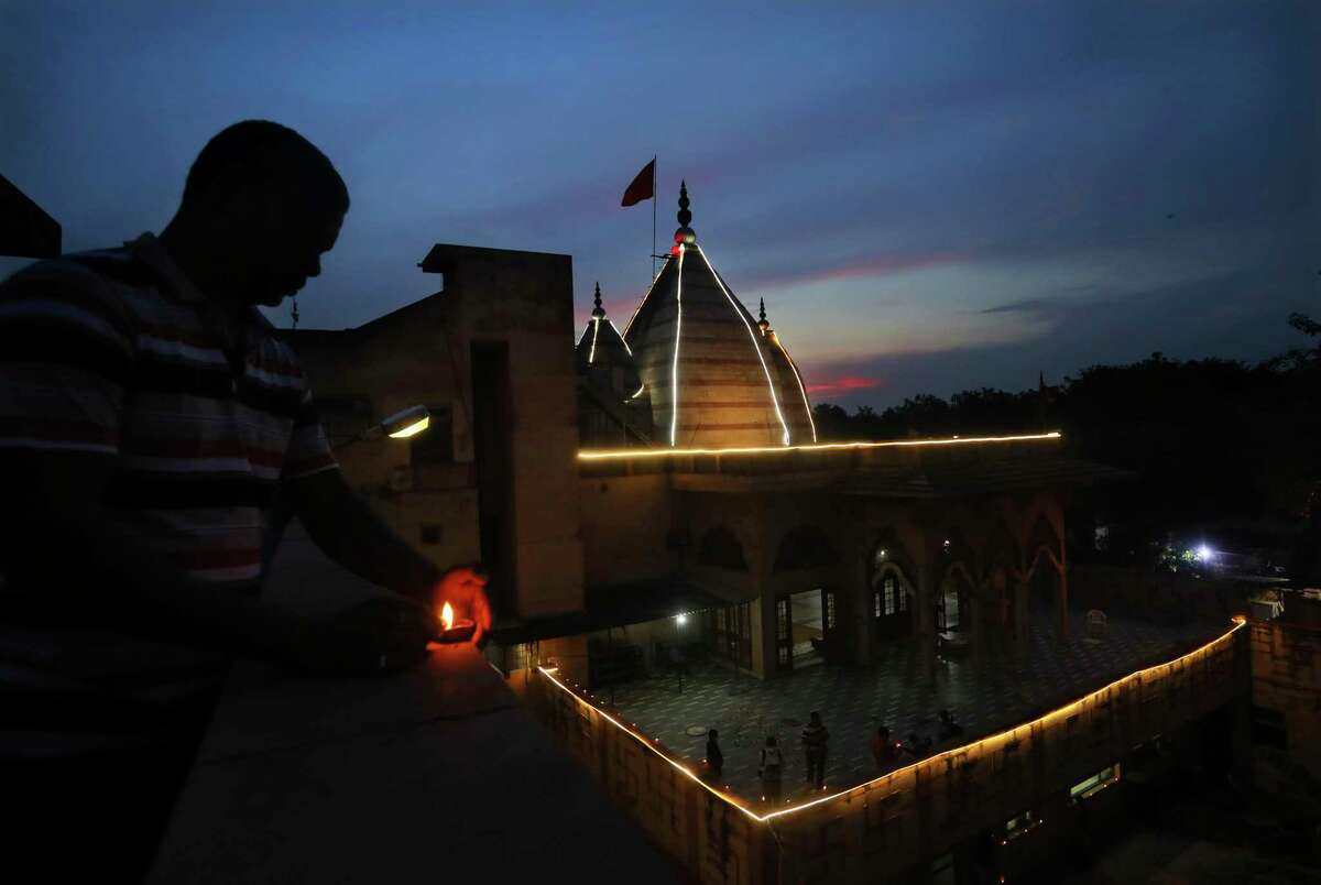 Indians light earthen lamps to celebrate groundbreaking ceremony of a temple dedicated to the Hindu god Ram by Indian Prime Minister Narendra Modi in Ayodhya, in New Delhi, India, Wednesday, Aug. 5, 2020. Hindus rejoiced as Modi broke ground on a long-awaited temple of their most revered god, Ram, at the site of a demolished 16th century mosque. (AP Photo/Manish Swarup)