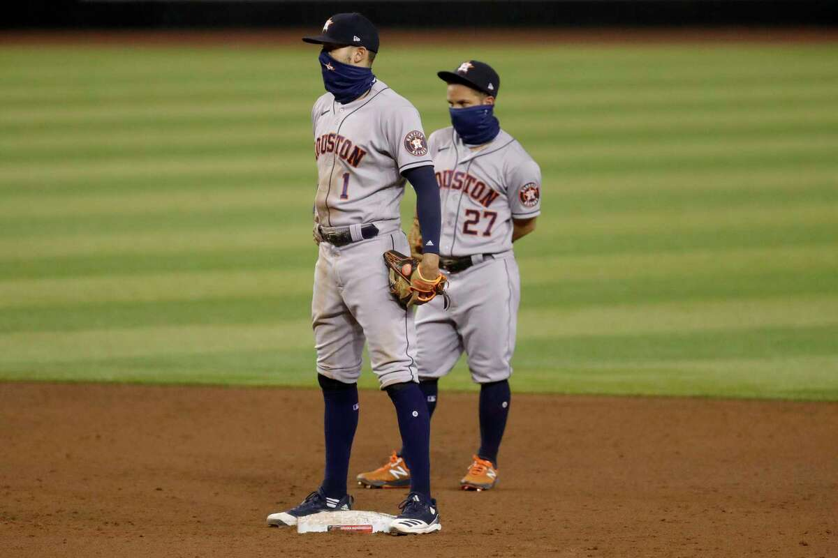 Houston Astros Carlos Correa (1) and Jose Altuve (27) wait between hitters during the sixth inning of a baseball game against the Arizona Diamondbacks Wednesday, Aug. 5, 2020, in Phoenix. (AP Photo/Matt York)