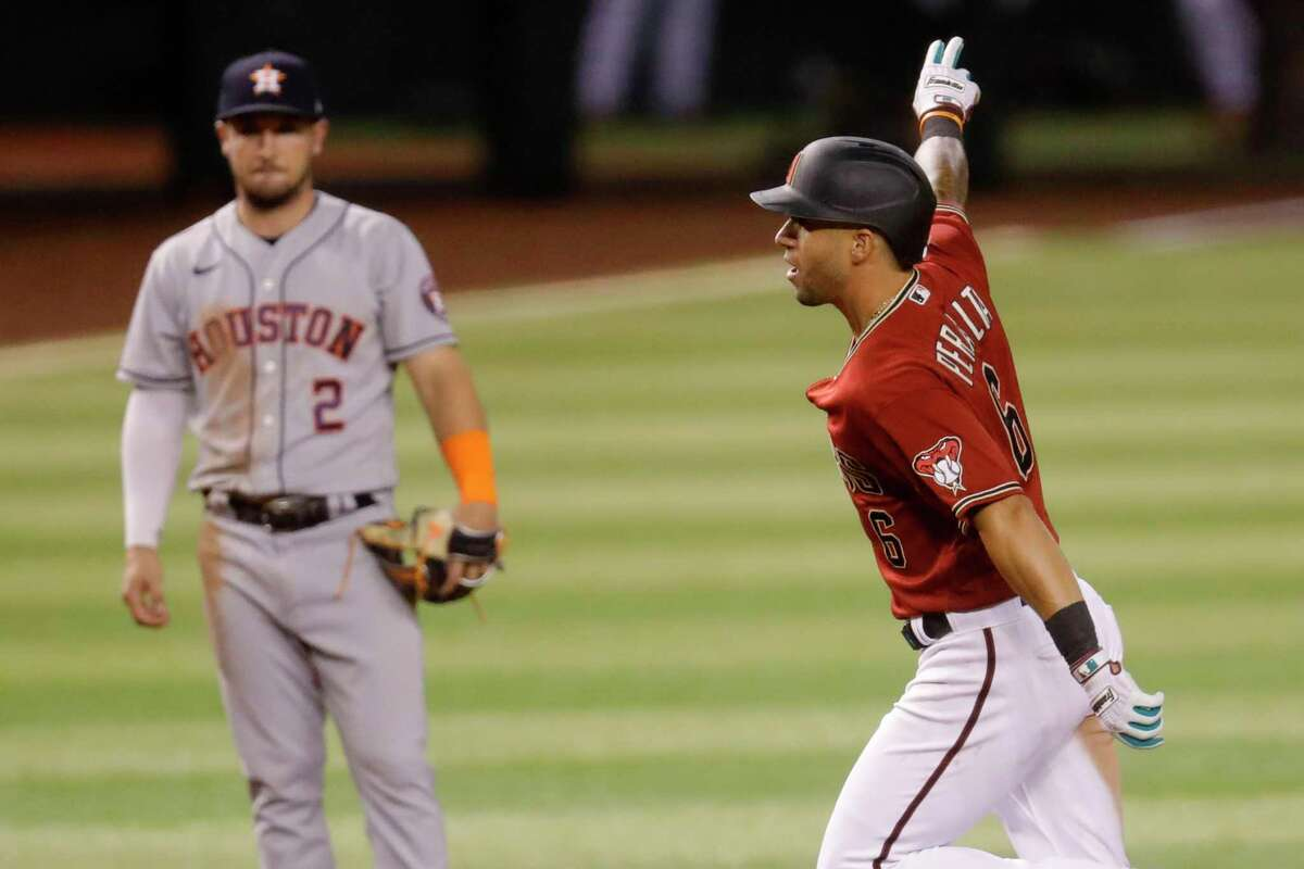 Arizona Diamondbacks' David Peralta celebrates as he rounds the bases after hitting a solo home run during the seventh inning of a baseball game Wednesday, Aug. 5, 2020, in Phoenix. Looking on is Houston Astros' Alex Bregman (2). (AP Photo/Matt York)
