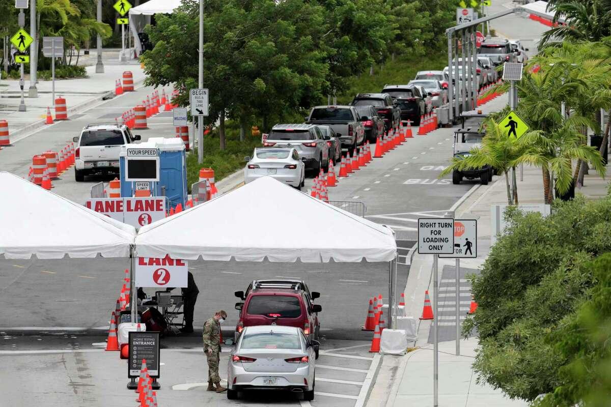 Vehículos esperan en cola en un sitio de pruebas de COVID-19 en el Miami Beach Convention Center durante la pandemia de coronavirus, el domingo, 12 de juio del 2020.
