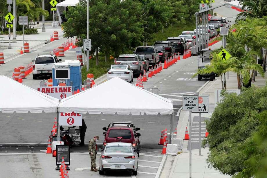 Vehículos esperan en cola en un sitio de pruebas de COVID-19 en el Miami Beach Convention Center durante la pandemia de coronavirus, el domingo, 12 de juio del 2020. Photo: Lynne Sladky /Associated Press / Copyright 2020 The Associated Press. All rights reserved.