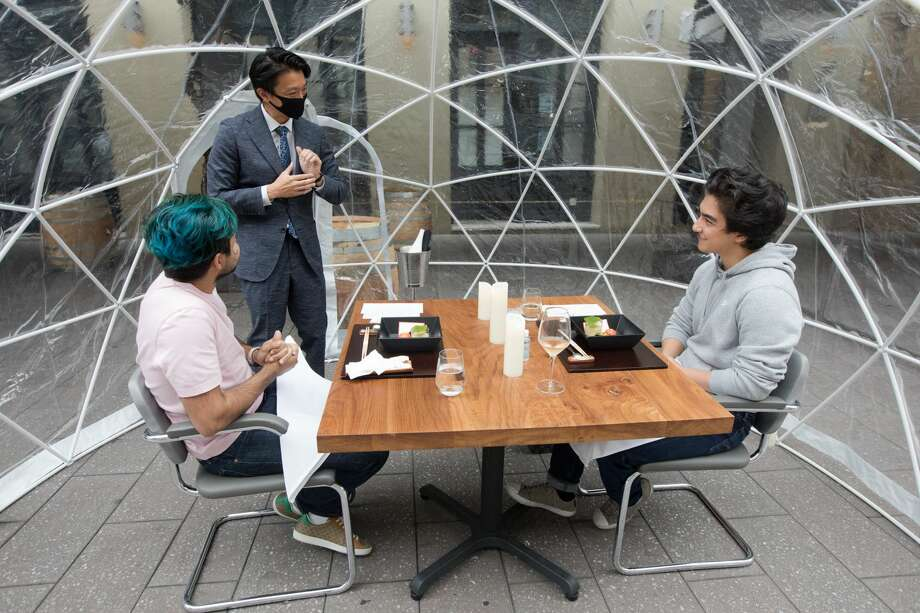 Waiter Masaaki Shijeno explains to diners (left to right) Al Habeeb and Ed Shehab what their first course consist of. Sushi Hashiri opened up outdoor dining service using patio bubbles in front of their restaurant in Mint Plaza in San Francisco, California on Aug. 5, 2020. Photo: Douglas Zimmerman/SFGATE / SFGATE