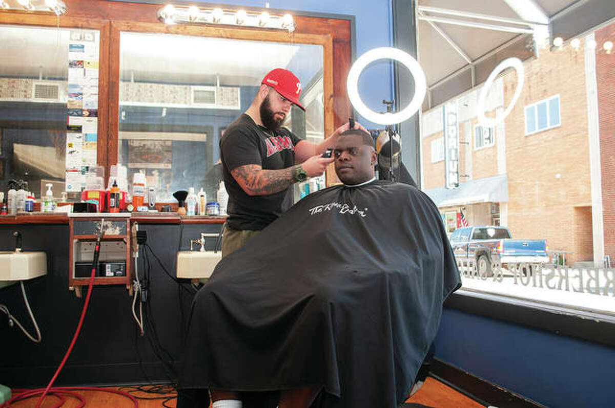 Connor Godar (left) works Wednesday on a fade for Braxton Criss at Uppercuts Barbershop & Salon at 206 E. Court St. A fade is a hairstyle that gradually shortens hair length from longer on top to shorter on bottom.