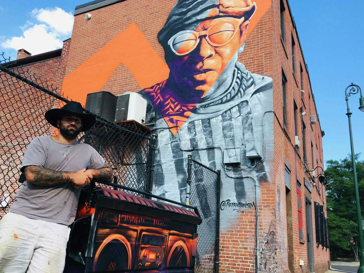 Artist Mike Deangelo, who goes by M. Deangelo, painted a three-story mural of the late, great avant-garde jazz musician Sun Ra on the back wall of the Cafe Nine building in New Haven all in one day. He put a cherry on top, painting the Cafe Nine dumpster to look like a boom box. Three murals were in the spotlight the other day in a Register article showing Michael DeAngelo and other artists working on the Straight Up Art project of the Town Green District in New Haven, which seeks to enhance the area by fostering neighborhood pride and presenting opportunities for local artists. Late-summer murals in the 9th Square are honoring Dave Higgins and Dr. Michelle Salazar, a CT Transit driver and surgery resident at Yale New Haven Hospital, respectively.