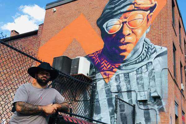 Artist Mike Deangelo, who goes by M. Deangelo, painted a three-story mural of the late, great avant-garde jazz musician Sun Ra on the back wall of the Cafe Nine building in New Haven all in one day. He put a cherry on top, painting the Cafe Nine dumpster to look like a boom box.
