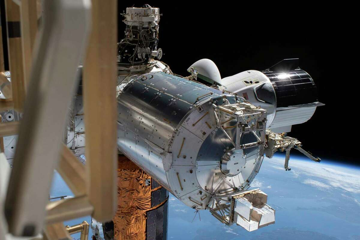 FILE - This July 1, 2020 photo made available by NASA shows the SpaceX Crew Dragon, right, docked to the International Space station, during a spacewalk conducted by astronauts Bob Behnken and Chris Cassidy.