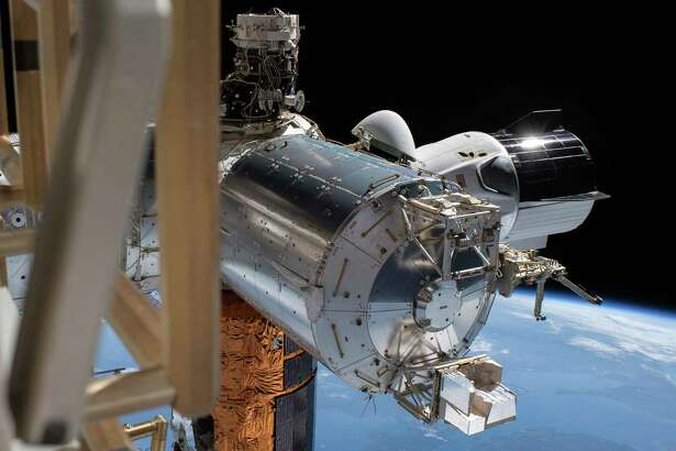This July 1, 2020 photo made available by NASA shows the SpaceX Crew Dragon, right, docked to the International Space station, during a spacewalk conducted by astronauts Bob Behnken and Chris Cassidy.