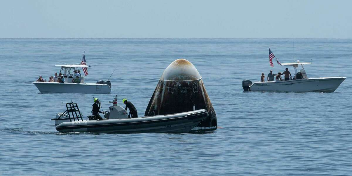 In this Sunday, Aug. 2, 2020, file photo, provided by NASA, support teams and curious recreational boaters arrive at the SpaceX Crew Dragon Endeavour spacecraft shortly after it landed with NASA astronauts Bob Behnken and Doug Hurley on board in the Gulf of Mexico off the coast of Pensacola, Fla.  - 1200x0 - Space race? America's new path to the ISS could affect relationship with Russia