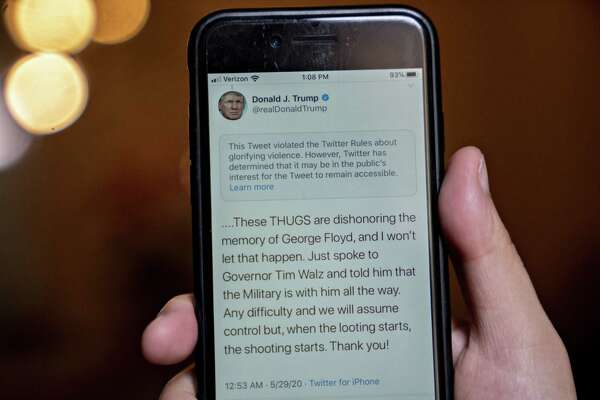 "A tweet by President Trump with a rule-violation notice that includes the phrase ""when the looting starts, the shooting starts"" on a smartphone in an arranged on May 29, 2020."