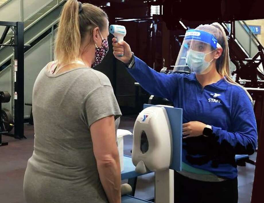 Two Fort Bend County YMCAs will soon offer Y Learning Centers, a newly-created virtual learning center designed to offer support to students taking online classes and assistance to families where parents must return to work this fall. In this file image, a YMCA staff member checks temperatures of guests as a newly-re-opened facility per CSC guidelines. Photo: Contributed Photo