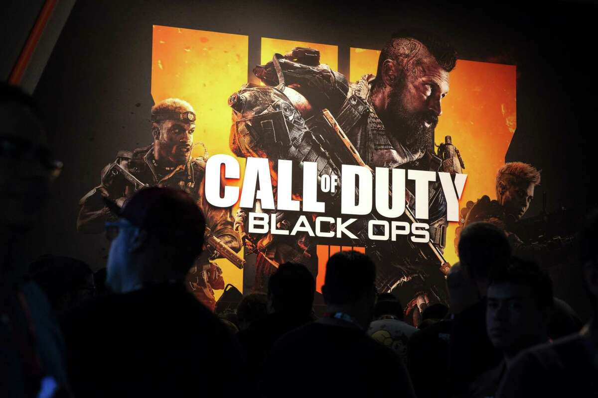 Attendees stand next to signage for Activision Blizzard's Call Of Duty: Black Ops 4 video game during the E3 Electronic Entertainment Expo in Los Angeles, California, on June 12, 2018.