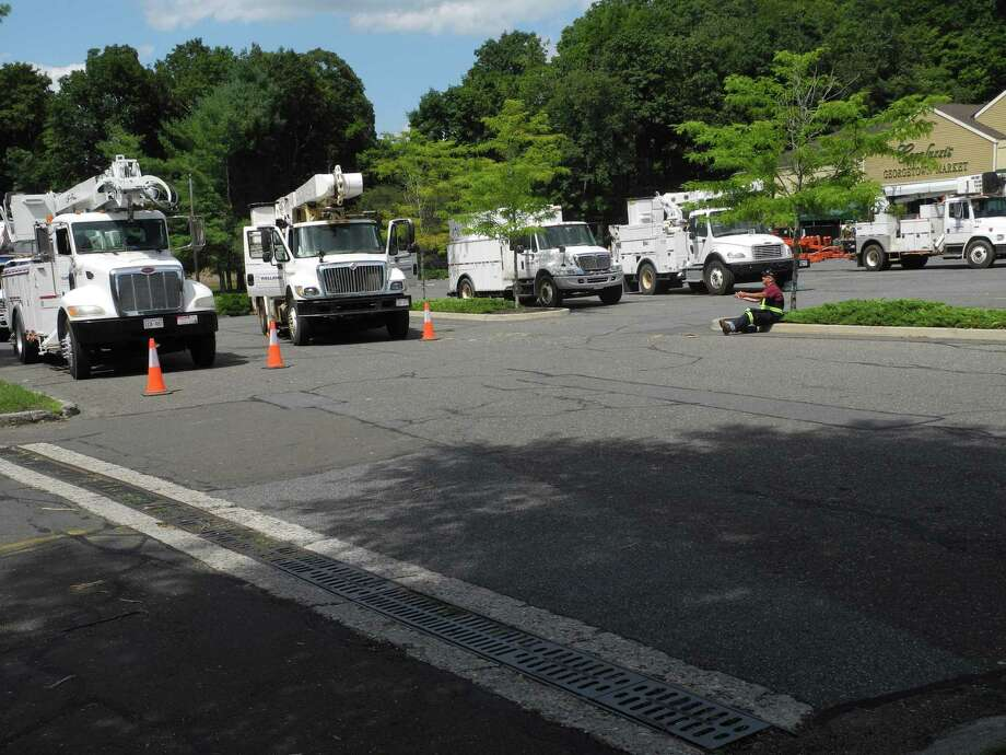 Crews with utility trucks down from Brunswick, Canada, await their orders Wednesday at Carluzzi's Georgetown Market in Wilton, Conn., on Aug. 5, 2020. Photo: Jeannette Ross / Hearst Connecticut Media / Wilton Bulletin