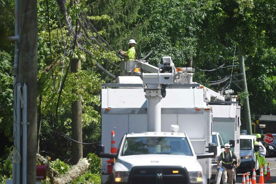 Crews repair power lines downed from tropical storm Isaias in Greenwich, Conn. Wednesday, Aug. 5, 2020. Tuesday's storm knocked down trees and powerlines throughout the state and power remains out in thousands of homes.