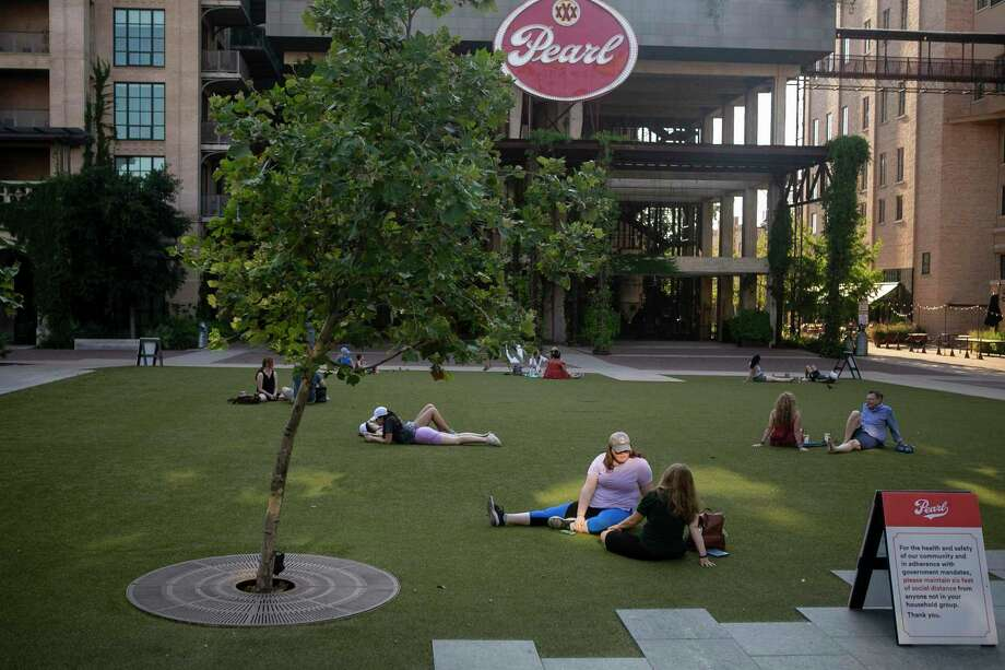 People lounge in the grass while social distancing at the Pearl in San Antonio, Texas on the evening of May 4, 2020. Photo: Josie Norris, The San Antonio Express-News / Staff Photographer / **MANDATORY CREDIT FOR PHOTOG AND SAN ANTONIO EXPRESS-NEWS/NO SALES/MAGS OUT/TV