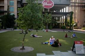 People lounge in the grass while social distancing at the Pearl in San Antonio, Texas on the evening of May 4, 2020.