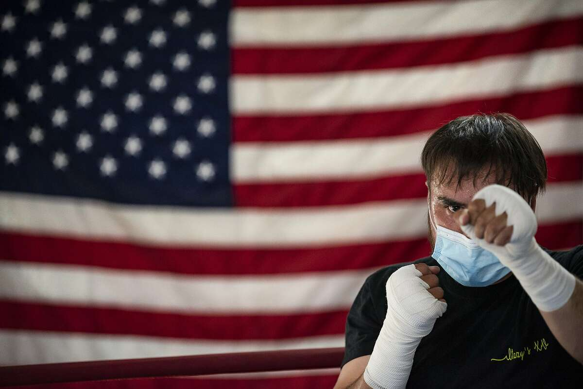 Victor Hernandez shadowboxes while wearing a mask, in front of a U.S. flag hanging on the wall of West Texas Knockout Boxing Club in Odessa, Texas, Tuesday, Aug. 4, 2020. The club had been closed since late March. (Eli Hartman/Odessa American via AP)