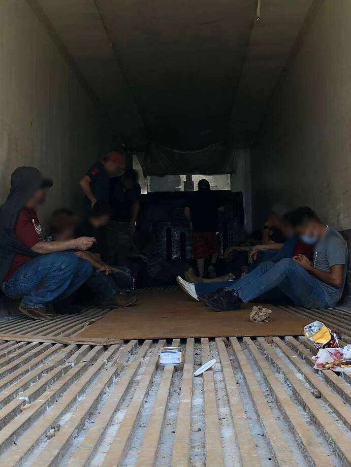 Shown are the 23 immigrants discovered inside the trailer of a truck that was stuck on railroad tracks near mile marker 14 of I-35. Photo: Courtesy