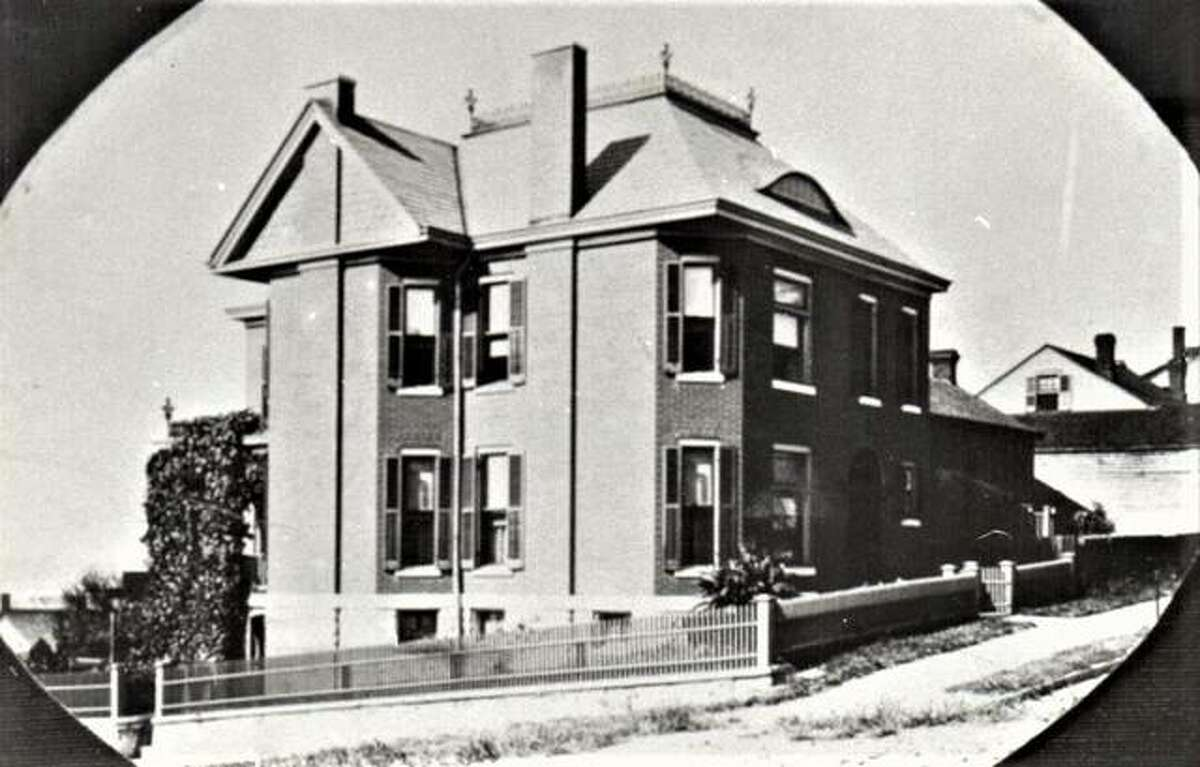 """The historic Koenig House, located at 829 E. 4th St, Alton and built in 1897, before the streets were bricked. Note the """"brow"""" window and the iron fence on the roof."""