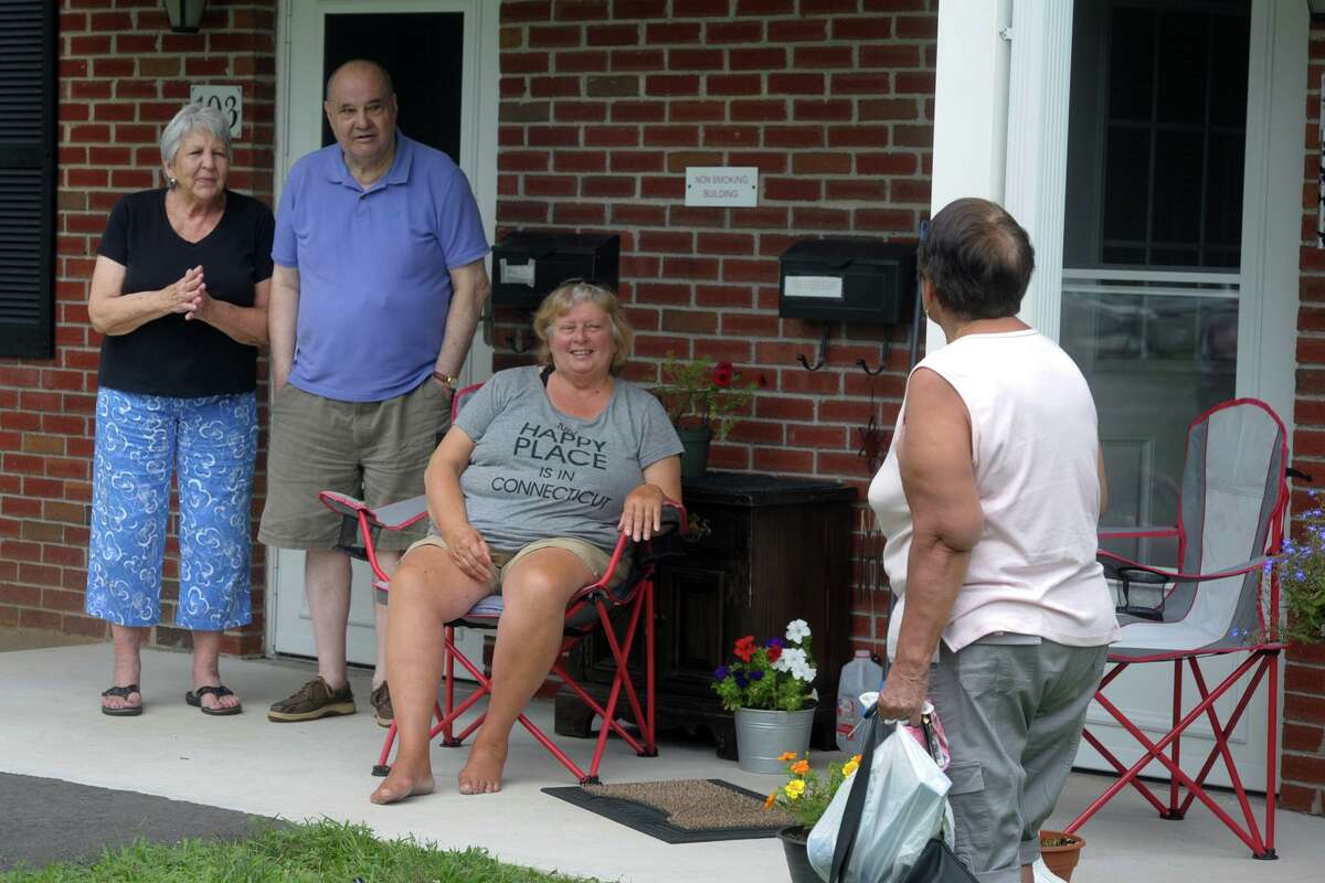 From left, Kathy and Bob Jevarjian, Alena Mammana and Gladys Martinez visit with each outside their homes in Stern Village, in Trumbull, Conn. Aug. 6, 2020. Stern Village remained without power on Thursday afternoon.