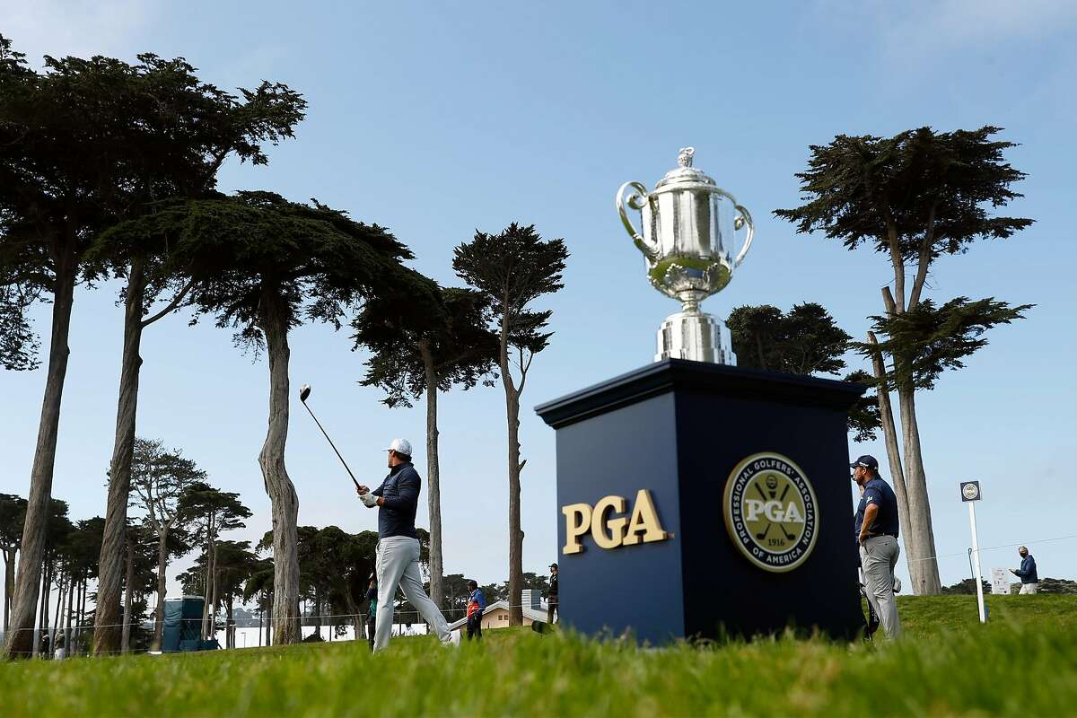 As the Wanamaker Trophy is displayed, behind him, 2-time defending champion Brooks Koepka tees off on the 1st hole during 1st round of PGA Championship at TPC Harding Park in San Francisco, Calif., on Thursday, August 6, 2020.