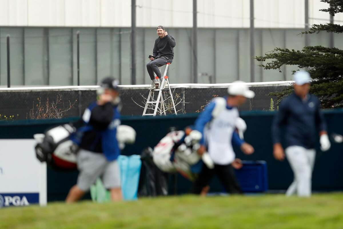 A fan watches from outside TPC Harding Park as Brooks Koepka leaves the tee box on the 13th hole during 1st round of PGA Championship in San Francisco, Calif., on Thursday, August 6, 2020.