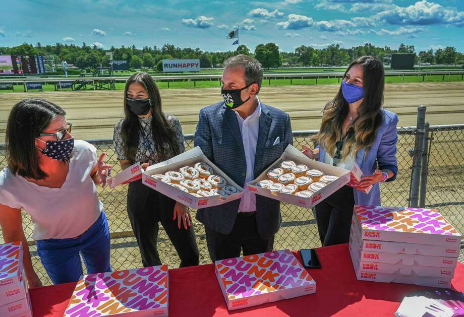 "In celebration of the 151st running of the Runhappy Travers at Saratoga Race Course, the New York Racing Association, Inc. will present the Backstretch Employee Service Team (BEST) with more than 350 ""Runhappy donuts"" and 750 Dunkin' gift cards, courtesy of champion sprinter Runhappy and Dunkin'. Accepting the donation representing BEST are from left, Nancy Underward, director BEST, Saratoga: Samira Bazoni, BEST andChristina Jordan, BEST intern and joining the BEST Team is Tony Allevato, chief revenue officer and president of NYRA Bests at the Saratoga Race Course Thursday Aug. 6, 2020 in Saratoga Springs, N.Y.  Photo by Skip Dickstein/Special to the Times Union Photo: Skip Dickstein / Skip Dickstein 2020"