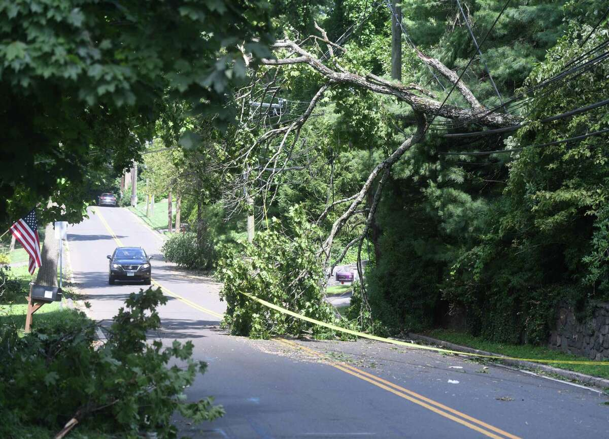 Cars are restricted to one lane as a downed tree from tropical storm Isaias remains on Brookside Drive in Greenwich, Conn. Wednesday, Aug. 5, 2020.