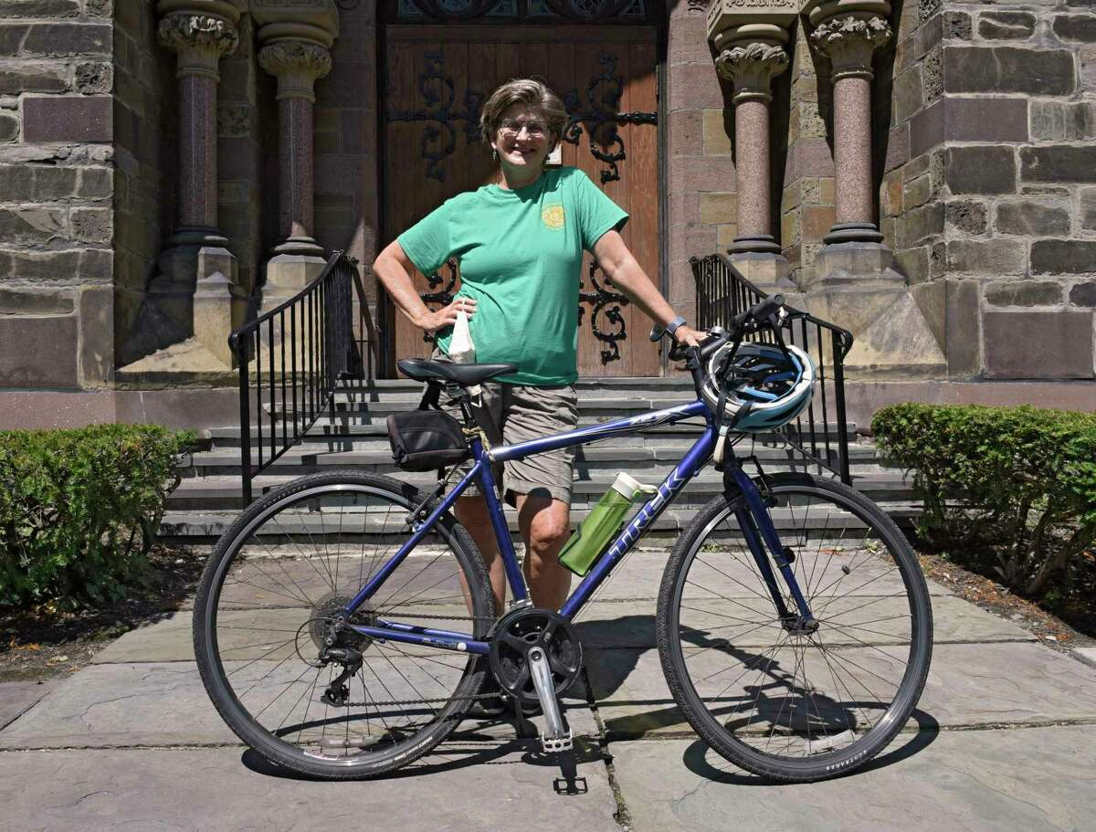 Caroline Brooks stands with her bike in front of First Reformed Church on Wednesday, Aug. 5, 2020 in Schenectady, N.Y. Caroline heads a committee that tries to help the very diverse congregation band together to curb plastic pollution, landfill overflow and dangers posed by PPE that's just tossed on the street or in parking lots. (Lori Van Buren/Times Union)