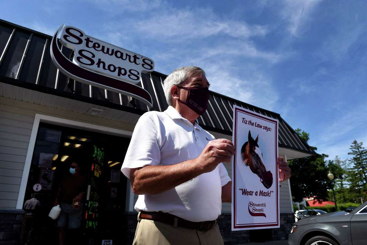 Jack Knowlton, owner of Belmont Stakes winner and Travers favorite, Tiz the Law, holds a new Stewart's Shops mask advisory sign featuring the local steed with coronavirus muzzle covering on Thursday, Aug. 6, 2020, at the Broadway and Circular Street Stewart's in Saratoga Springs, N.Y. (Will Waldron/Times Union)
