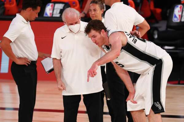 LAKE BUENA VISTA, FLORIDA - AUGUST 05: San Antonio Spurs center Jakob Poeltl #25 talks with head coach Gregg Popovich during the first half of a NBA basketball game against the Denver Nuggets at HP Field House at ESPN Wide World Of Sports Complex on August 5, 2020 in Lake Buena Vista, Florida. NOTE TO USER: User expressly acknowledges and agrees that, by downloading and or using this photograph, User is consenting to the terms and conditions of the Getty Images License Agreement. (Photo by Kim Klement-Pool/Getty Images)