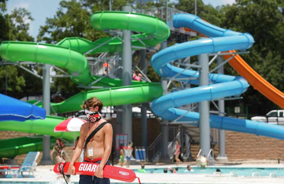 Lifeguard Zachary Clark wears a face mask as he monitors visitors to Conroe's new $5.4 million waterpark opened to the public, Wednesday, Aug. 4, 2020, in Conroe. The waterpark is opened daily from 11:00 a.m. to 6:00 p.m. features a children's pool, playground, a youth-adult pool and five water slides. Tickets are $8 per person with visitors allowed to bring coolers and food. Photo: Jason Fochtman, Houston Chronicle / Staff Photographer / 2020 © Houston Chronicle