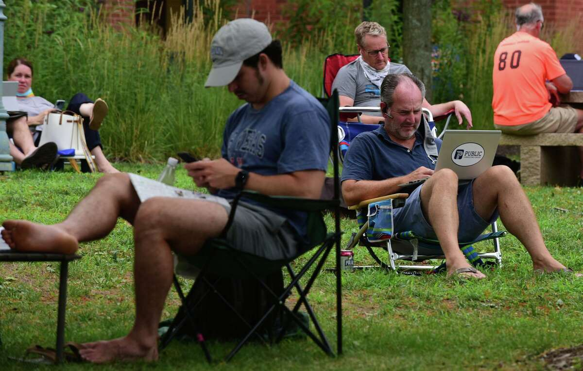 Over a hundred local residents crowd the outside of the Westport Public Library utilizing the WIFI and power outlets Thursday, August 6, 2020, in Westport, Conn. Residents continue to struggle with power outages following the tropical storm Tuesday.