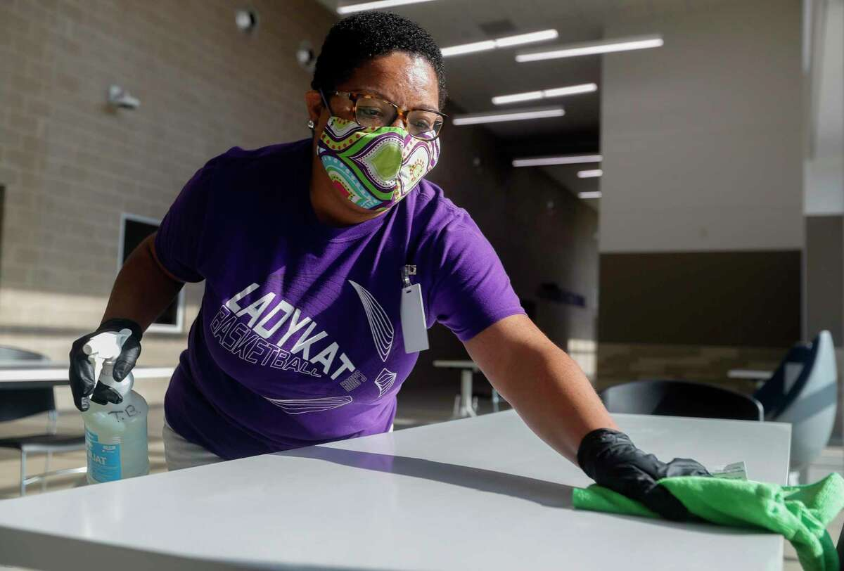 Tiffany Blackman cleans a table Thursday at Willis ISD's Career and Technology Education Center.