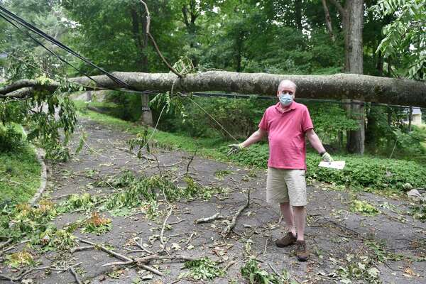 Mike Tebbs points out a tree downed during tropical storm Isaias that remains blocking a multi-family driveway in northern Stamford, Conn. Thursday, Aug. 6, 2020. Tuesday's powerful storm downed trees and powerlines and power remains out for thousands of Eversource customers throughout the region.