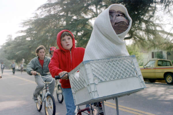 This undated studio handout shows Elliott, played by Henry Thomas, his brother and friends riding as fast as they can from the police to get 'E.T. The Extra-Terrestrial' back to the forest. Steven Spielberg's 1982 'E.T. The Extra-Terrestrial' returns to theaters Friday, updated with a couple of previously unreleased scenes, visual enhancements, improved sound and excisions that have annoyed some purists who dislike tampering with beloved films. (AP Photo/Bruce McBroom, Universal Studios Amblin Entertainment)