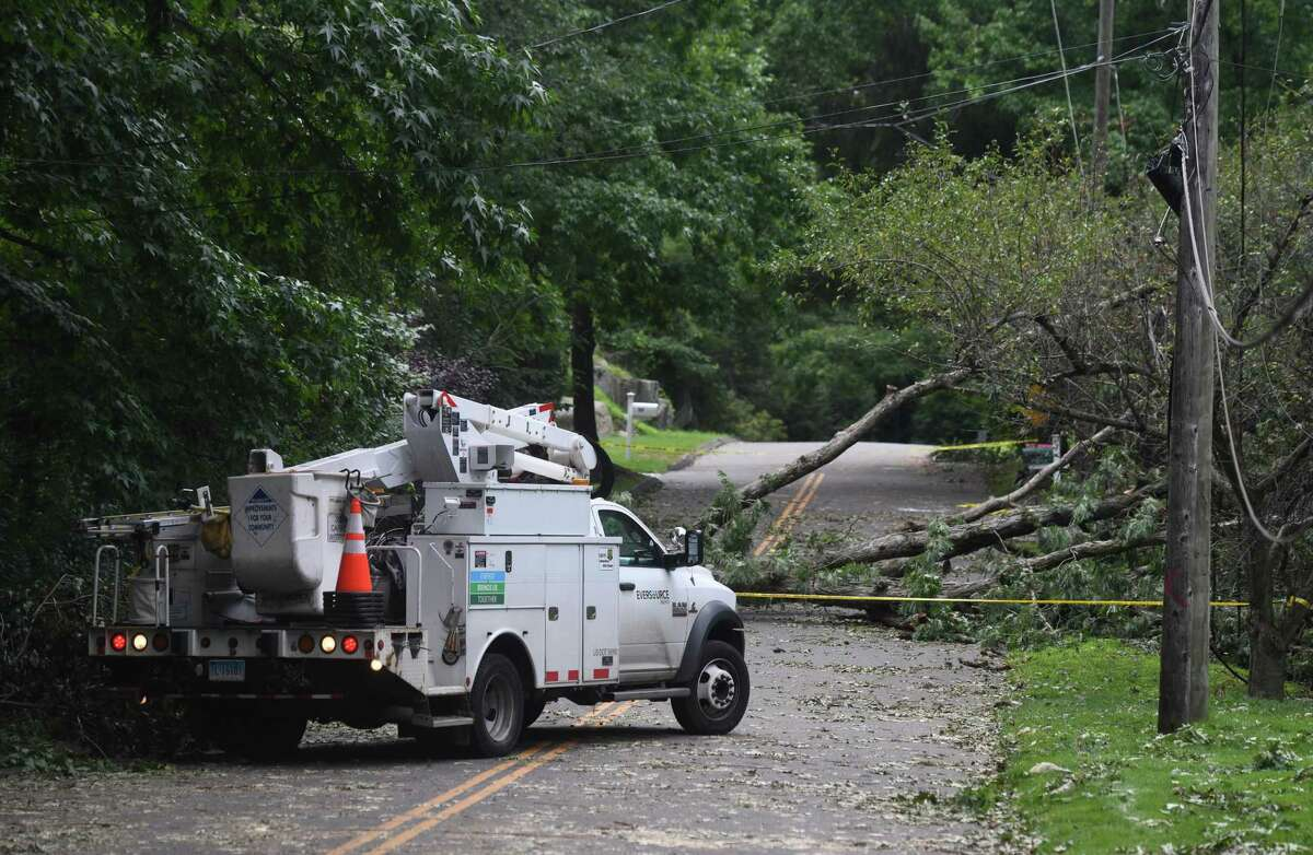 An Eversource truck surveys damage of a downed tree on Clover Place in the Cos Cob section of Greenwich, Conn. Thursday, Aug. 6, 2020. Tuesday's powerful storm downed trees and powerlines and power remains out for thousands of Eversource customers throughout the region.