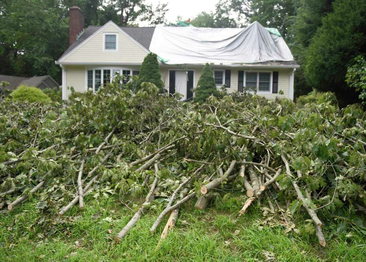 A tree is broken down after causing damage to a home on Mianus View Terrace in the Cos Cob section of Greenwich, Conn. Thursday, Aug. 6, 2020. Tuesday's powerful storm downed trees and powerlines and power remains out for thousands of Eversource customers throughout the region.