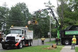 Crews were at work cleaning up downed trees and wires on Main Street, near Rockwell Road, on Thursday.