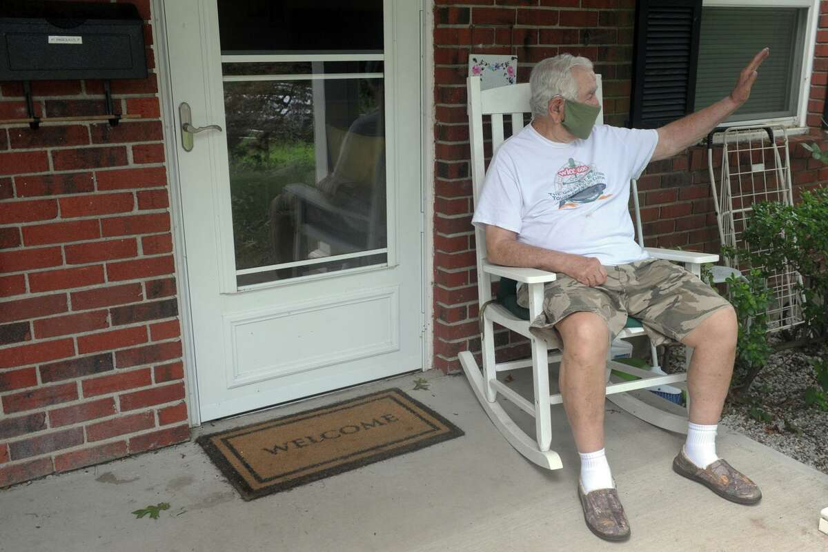 Resident Edward Bardinelli waves to a neighbor from his porch in Stern Village, in Trumbull, Conn. Aug. 6, 2020. Stern Village remained without power on Thursday afternoon.